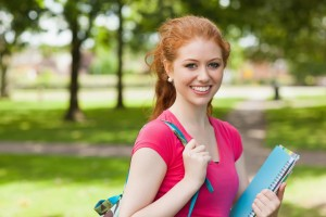 Gorgeous smiling student holding notebooks looking at camera on campus at college